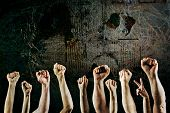 Arms raised in protest on a grunge background