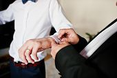 Best Man Helped Stylish Groom Wear Cuff Links At Wedding Day. poster
