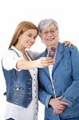 Mother and attractive young daughter taking photo of themselves by mobile phone, smiling happily.?