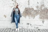 Hipster girl wearing blank gray t-shirt, jeans and coat posing against rough street wall, minimalist poster