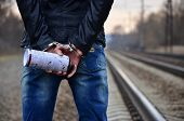 Girl In Handcuffs With Spraycan On The Background Of A Railway Track poster