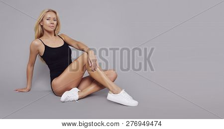 poster of Young Fitness Blonde Girl With Sporty Body Posing At Studio. Beautiful Fit Girl. Fitness Model In Bl