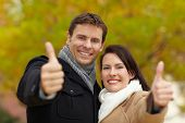 Happy smiling couple in autumn holding their thumbs up