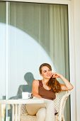 Thoughtful Pretty Woman With Cup Of Coffee Sitting On Terrace