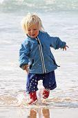 Cute little blonde boy running in the water from the atlantic ocean