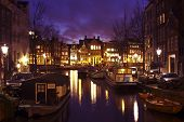 Amsterdam innercity in the Netherlands at twilight with houseboats and medieval houses
