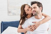 Woman Tenderly Embracing And Kissing Handsome Man In Bed poster