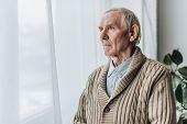 Upset Retired Man With Dementia Disease Standing At Home poster