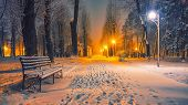 Winter Park With Benches Covered With Snow In The Evening. Winter Evening In A Central Park. poster