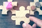 The House And Coins Are Placed On A Piece Of Puzzles With Last Piece With Text Mortgage. Concept Rea poster