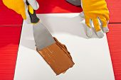 stock photo of grout  - Worker With Trowel Check On White Paper Mixing Grout - JPG