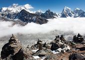 view of everest with stone mans from gokyo ri and clouds above ngozumba glacier