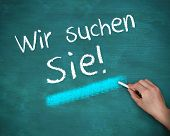 Hand writing wir suchen sie on blue background