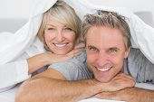 stock photo of pajamas  - Couple smiling under the covers at home in bed - JPG