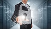 stock photo of lock  - Businessman selecting a futuristic padlock with a data center on the background - JPG