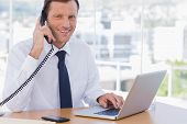 Smiling businessman posing while he is on the phone in his office