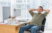 Smiling designer leaning back at his desk in a modern office