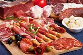 Sliced prosciutto di Parma on wooden board with olives and rosemary