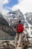 Hiking man with rucsac backpack standing on tree log by Moraine Lake looking at snow covered Rocky M