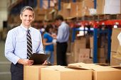 image of warehouse  - Manager In Warehouse Checking Boxes - JPG