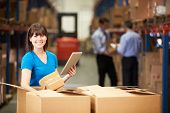 stock photo of warehouse  - Worker In Warehouse Checking Boxes Using Digital Tablet - JPG