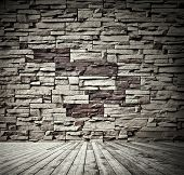 Background of aged grungy textured black brick and stone wall with light wooden floor with blackboar