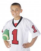 Waist-length image of a handsome elementary boy happily carrying his green football.  On a white background.
