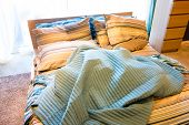 image of pillowcase  - a cozy and warm bed in a domestic bedroom with a big window - JPG