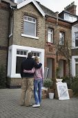 picture of possess  - Rear view of a couple looking at house with possessions outside - JPG