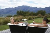 Side view of two young women taking bath with champagne on porch against mountains