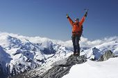 Male mountain climber raising hands with icepick on top of snowy peak