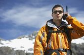 Smart young man using walkie talkie against blurred snow capped mountain