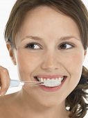 Closeup of a young woman brushing teeth against white background
