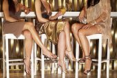stock photo of legs crossed  - Low section of three stylishly dressed women sitting legs crossed at the bar - JPG
