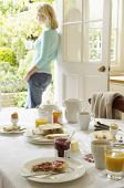 Woman holding tea at the doorway with breakfast table in foreground