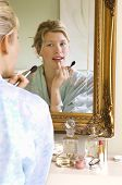 Reflection of a young woman in bathrobe sitting and applying makeup