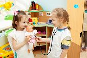 Child in kindergarten. Kids in nursery school. Girl playing with doll at infant school