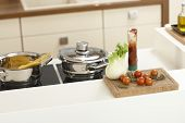 Closeup kitchen worktop with vegetables and saucepan on ceramic hob.