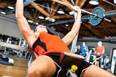 stock photo of yoke  - Man lifting a yoke in a fitness club - JPG