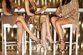 picture of crossed legs  - Low section of three stylishly dressed women sitting legs crossed at the bar - JPG