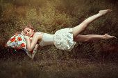 stock photo of levitation  - Levitation girl on a bed in a sweet dream - JPG