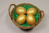 Four Golden Eggs In Basket On Green Grass