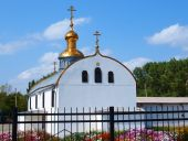A white chapel with golden domes