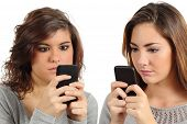 stock photo of adolescence  - Two teenagers addicted to the smart phone technology isolated on a white background - JPG