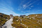 Hikers Reaching The Summit Of A Ridge With Cradle Mountain In Background.