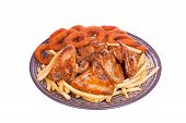 Grilled chicken wings with French fries and onions rings