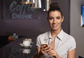 Attractive businesswoman using mobilephone, sitting in bar, smiling, looking at camera.