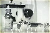 Vintage Still Life With Homeopathy Globules, Syringe With Blood And Microscope