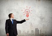 Young businessman holding electric bulb in palm