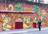 Businessman walking in front of a Graffiti Wall in Brooklyn.